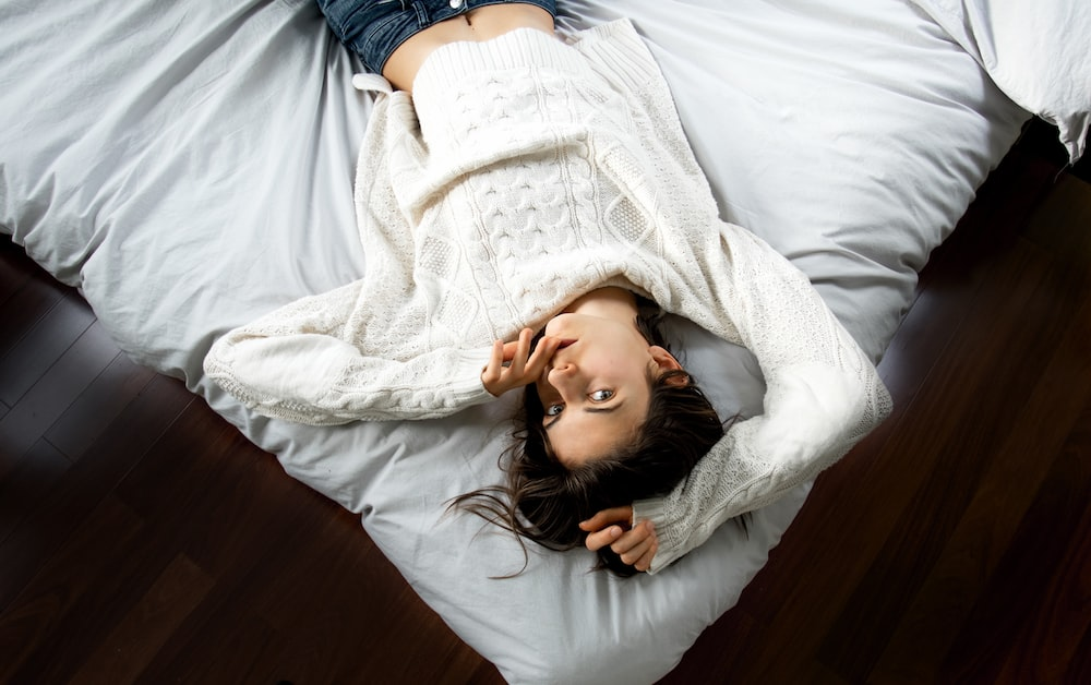 woman lying on bed with white bedspread
