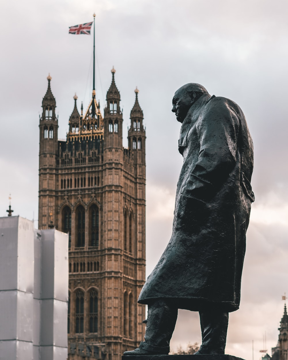 man wearing coat statue showing building with flag