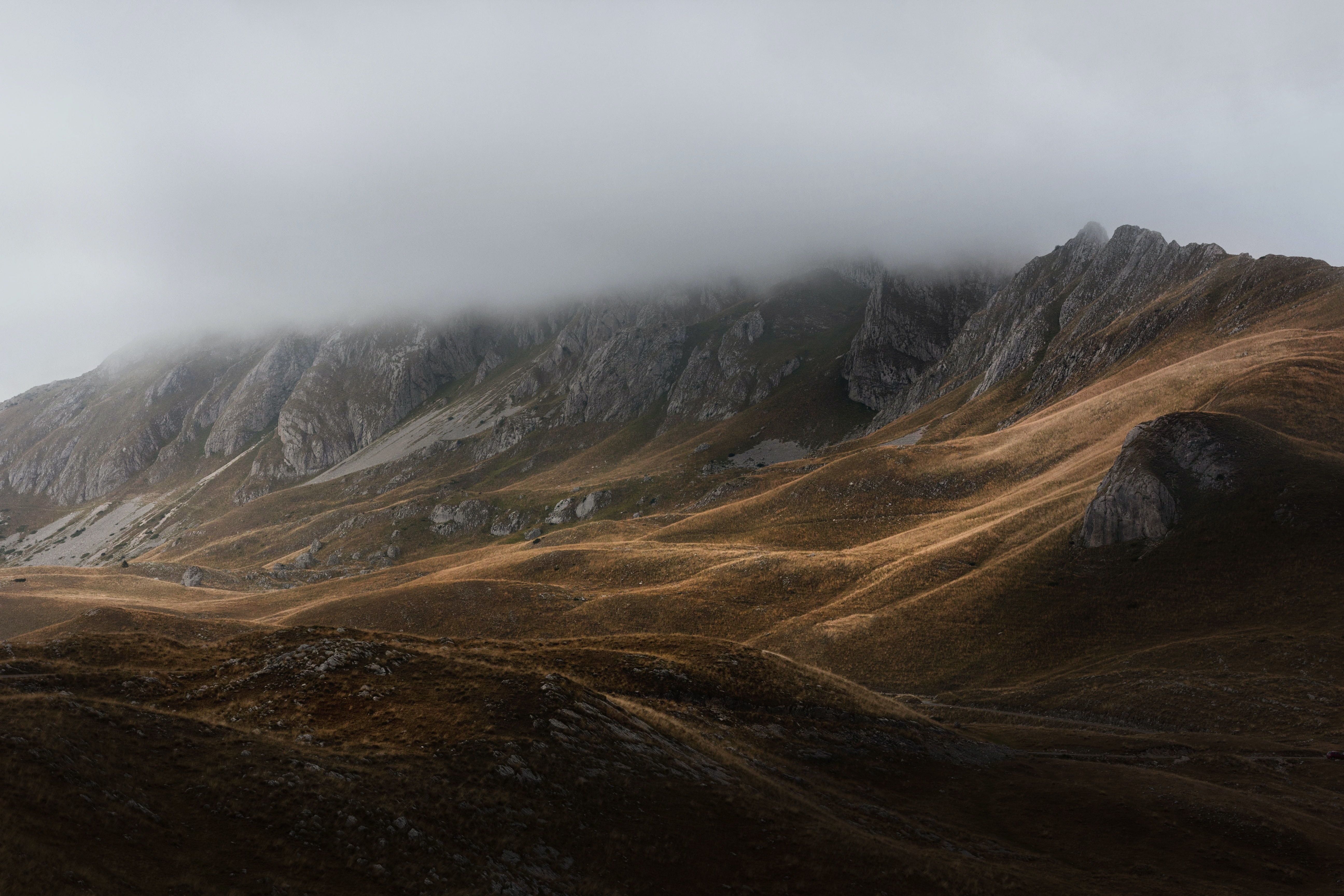 landscape photography of grey mountain under white clods
