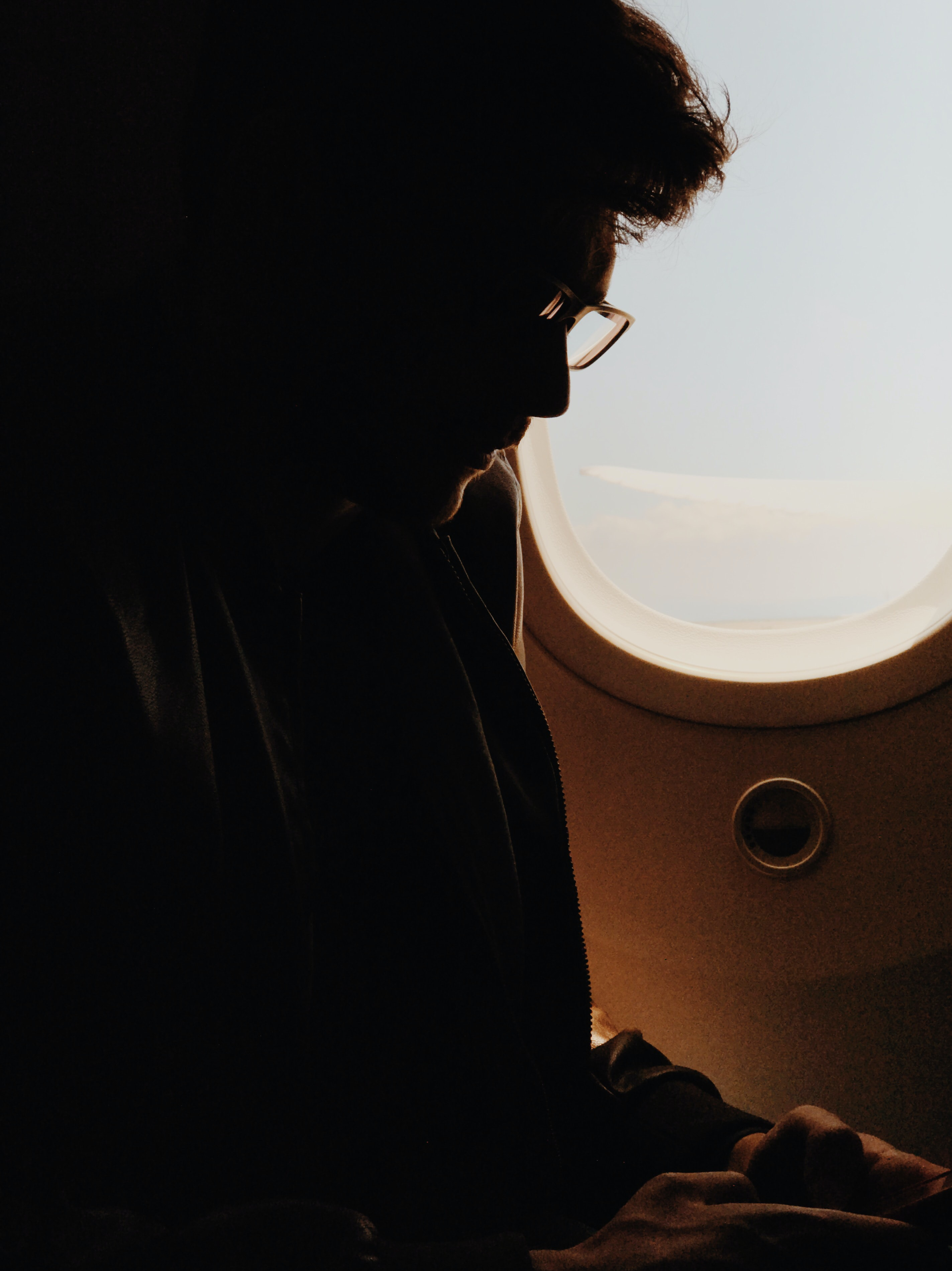 silhouette photography of man sitting in airplane seat
