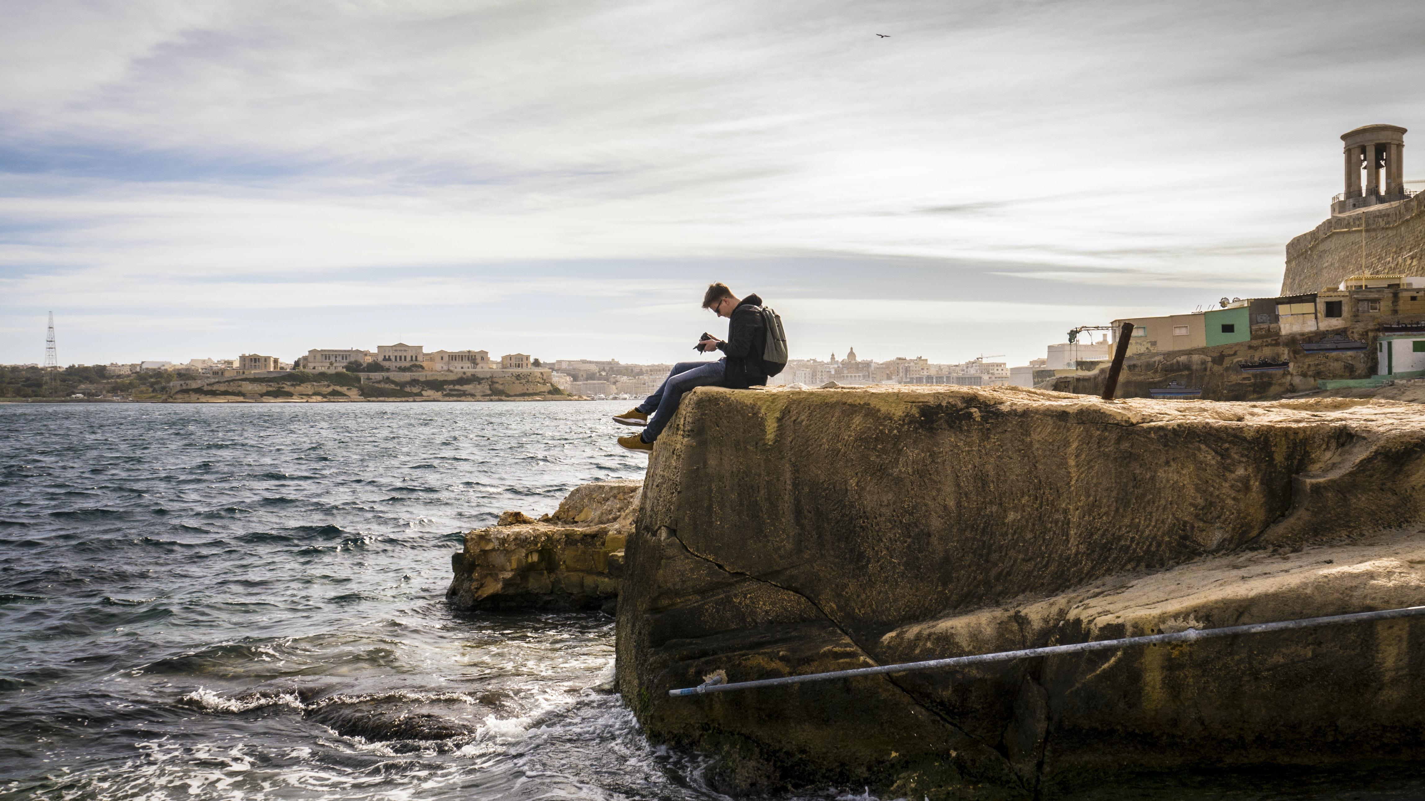 man sitting on brown rock near sea at daytime