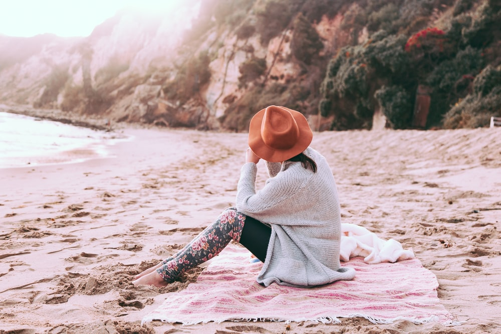photo of person sitting on sand at seashore
