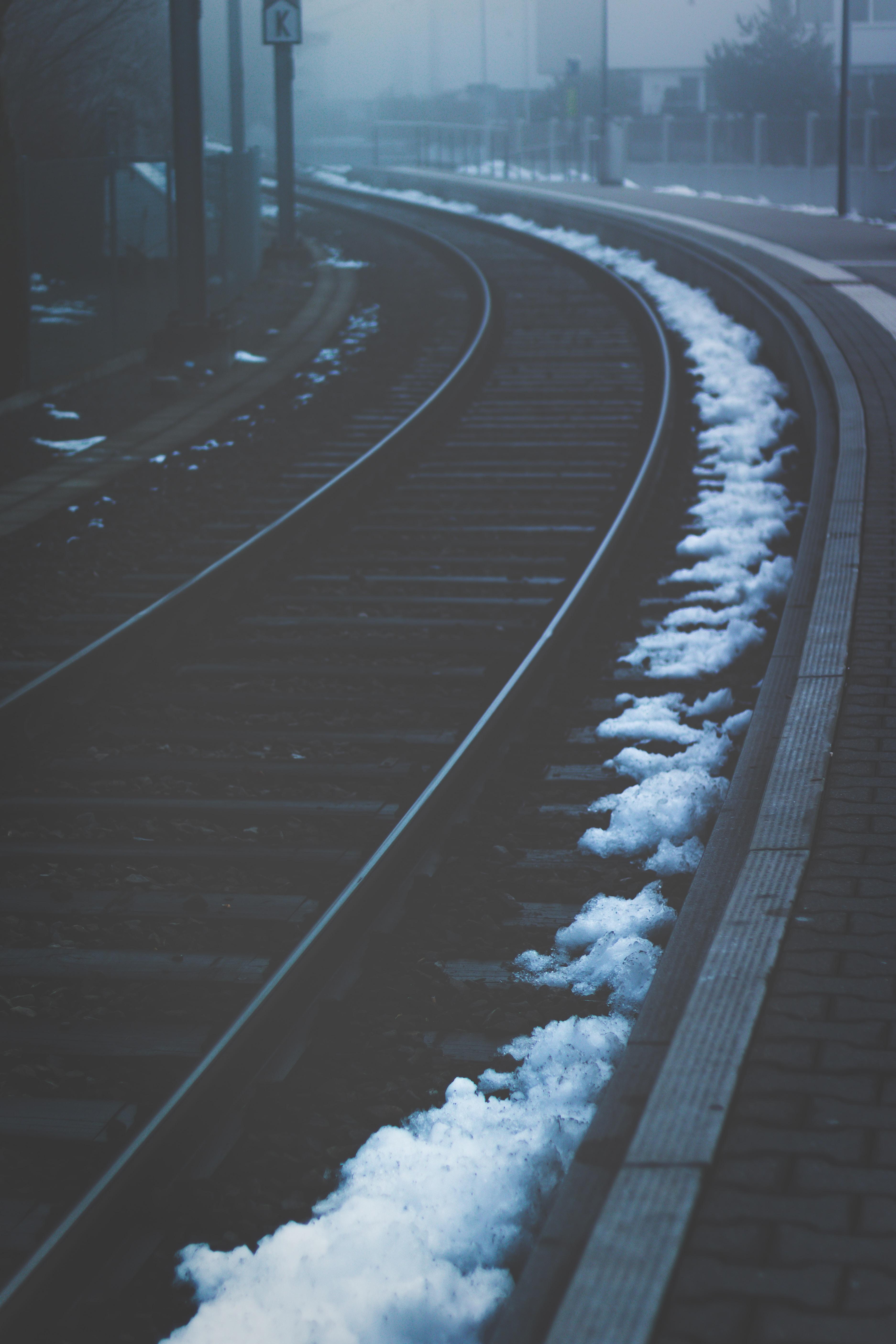 low light photography of train rails under foggy sky