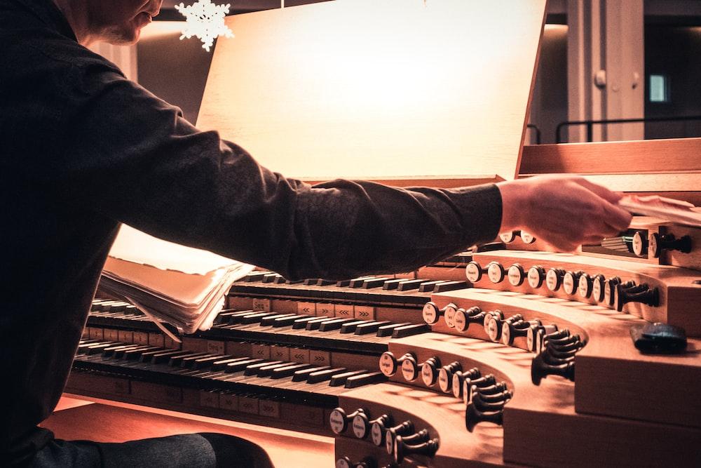 man playing brown musical instrument