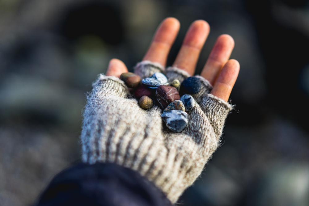 selective focus photo of person wearing gray knit fingerless glove holding stones