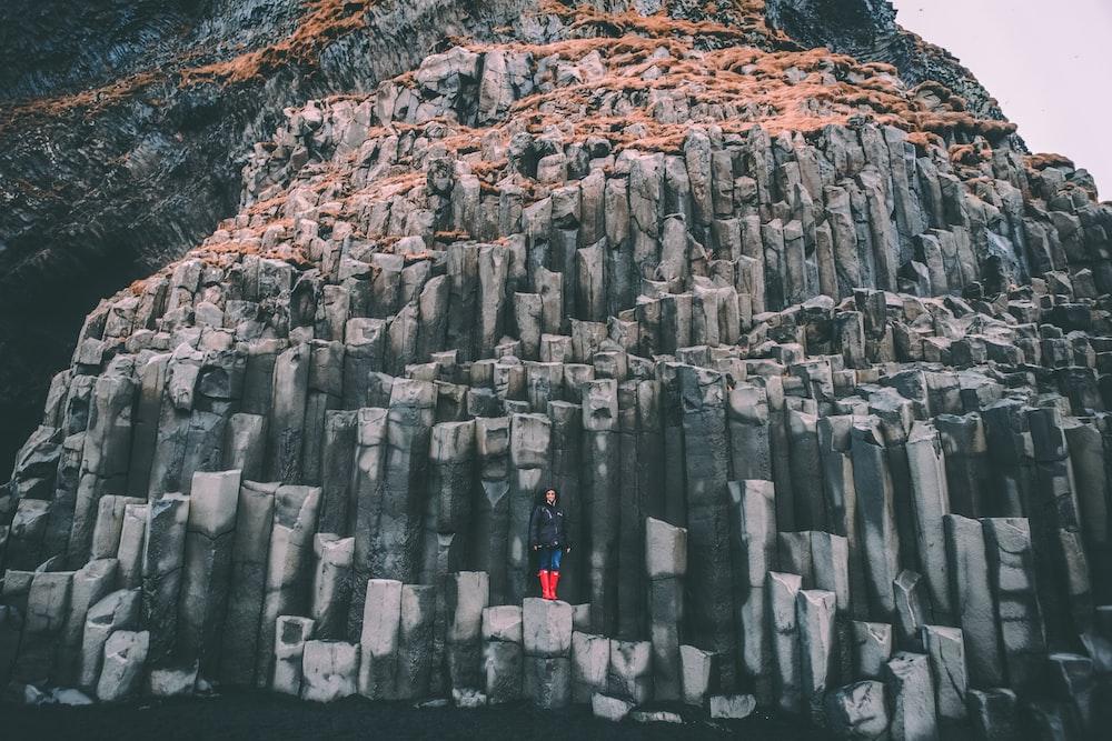 woman standing on grey rock mountain