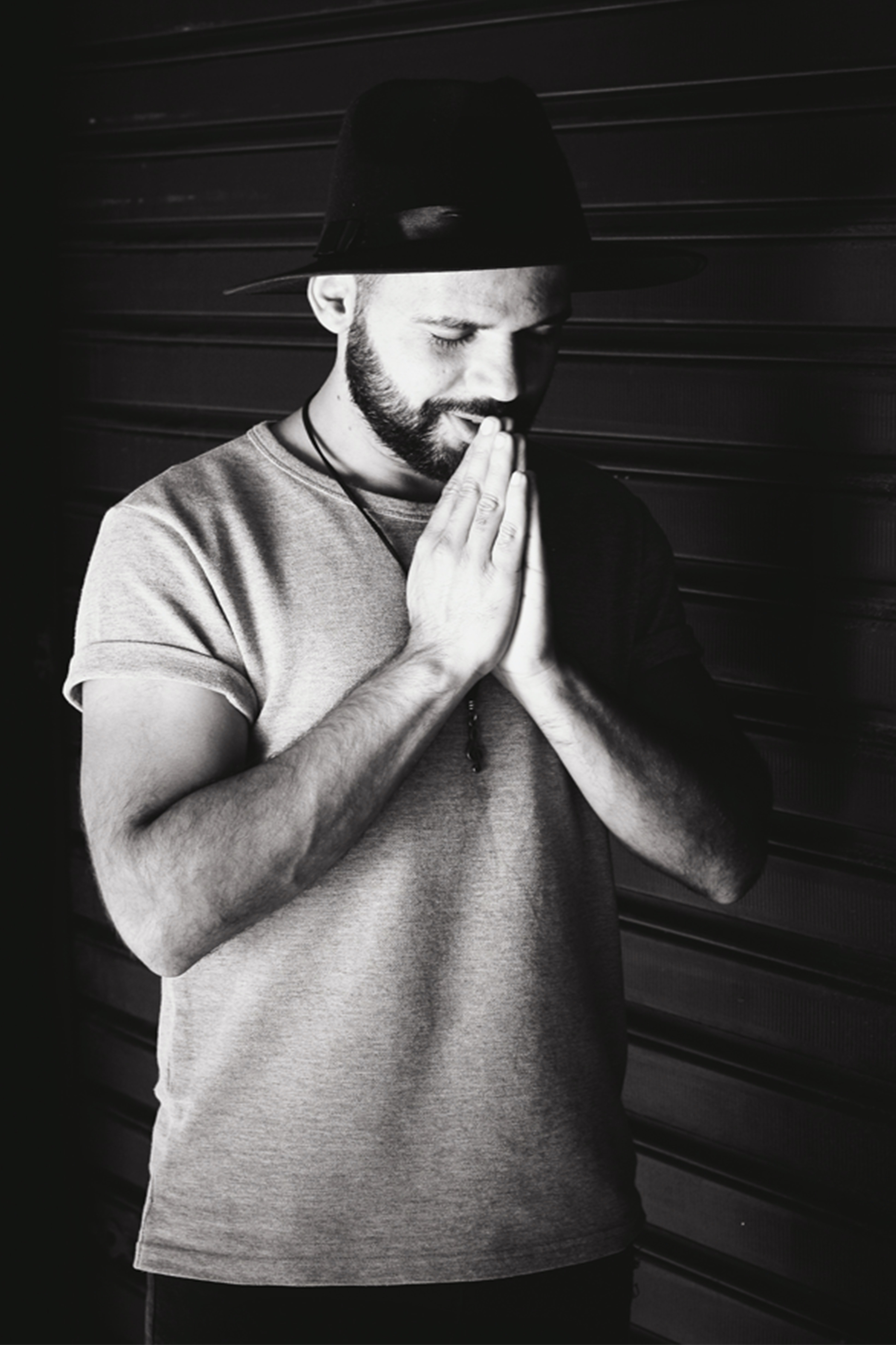 grayscale photography of a man praying