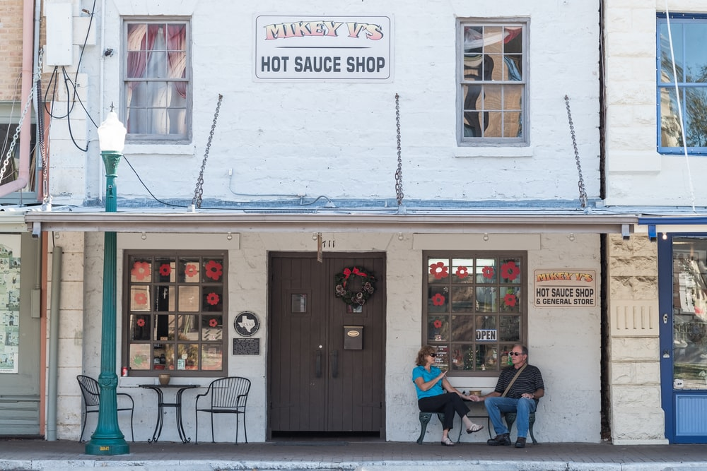 man and woman sitting in front of Hot Sauce Shop storefront