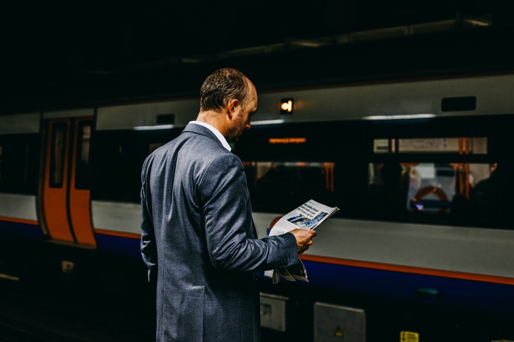 man holding newspaper standing on train station