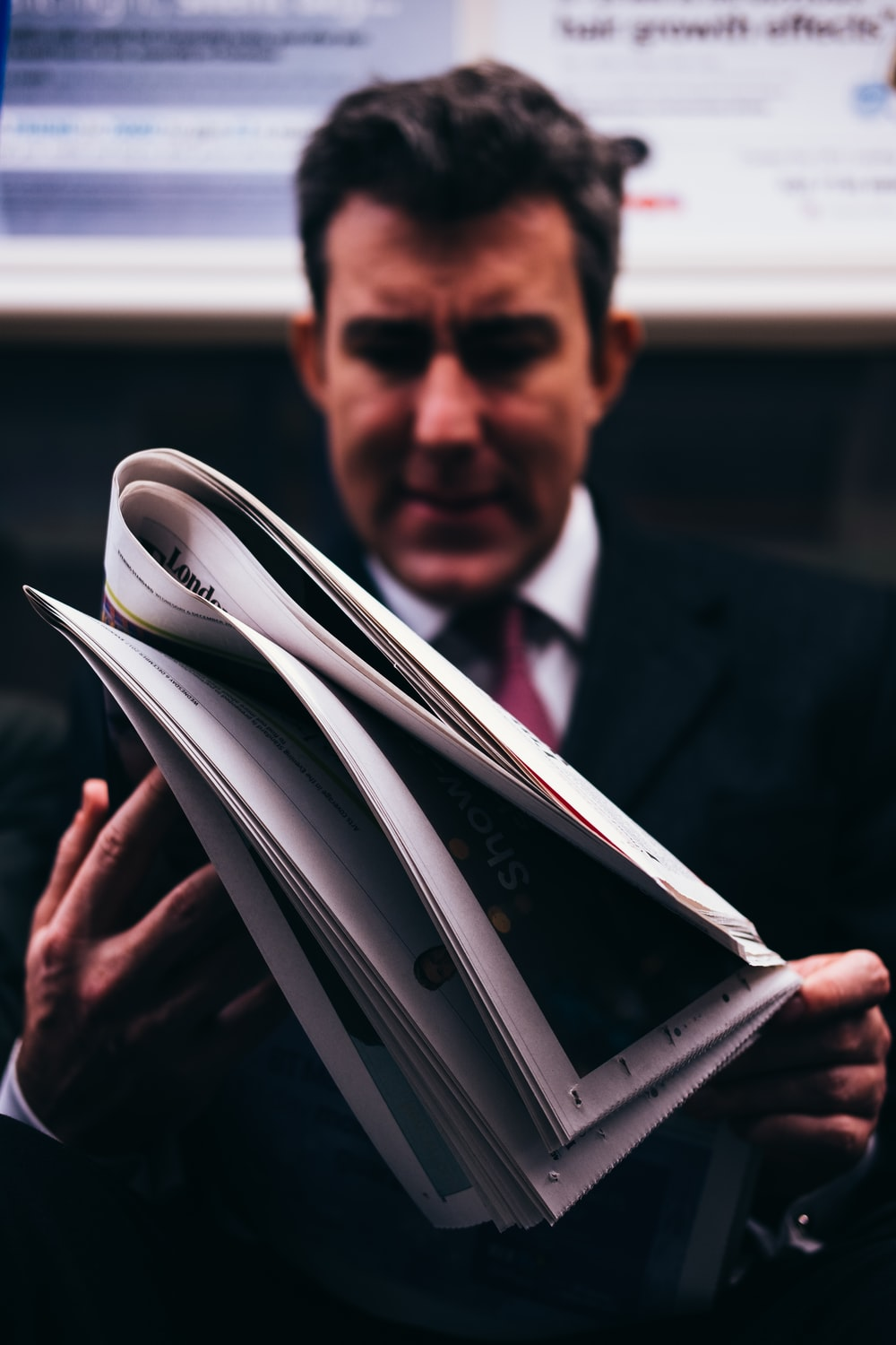 selective focus photo of man in suit holding newspaper
