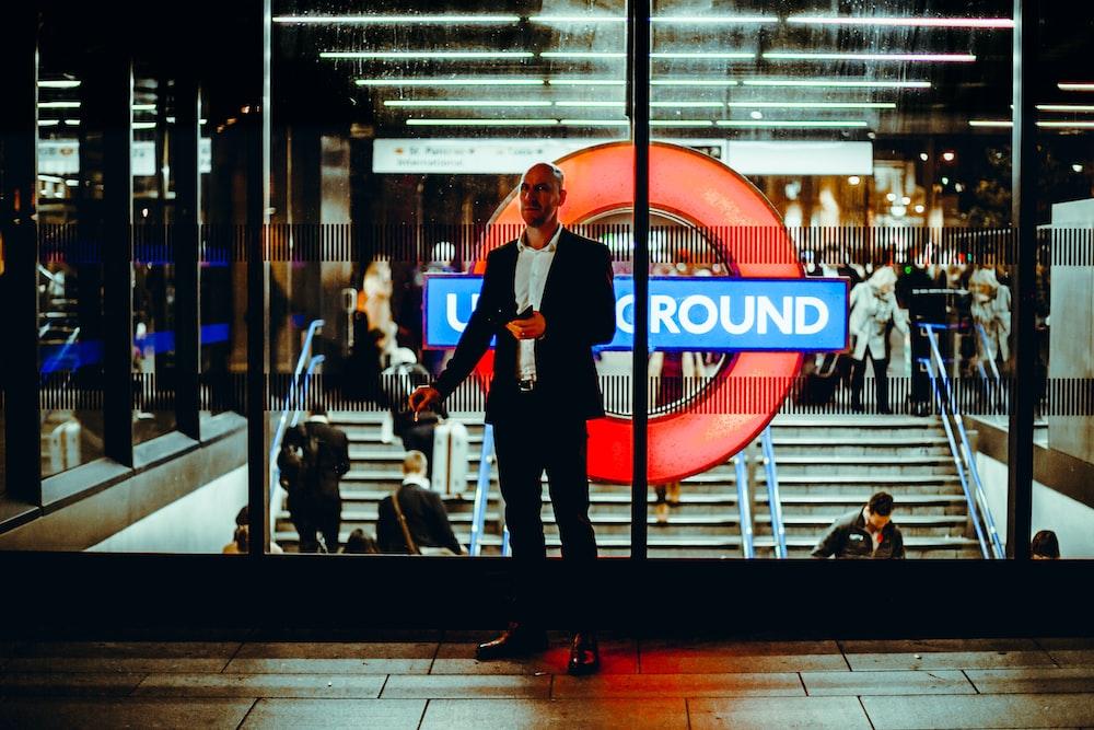 photo of man standing near glass