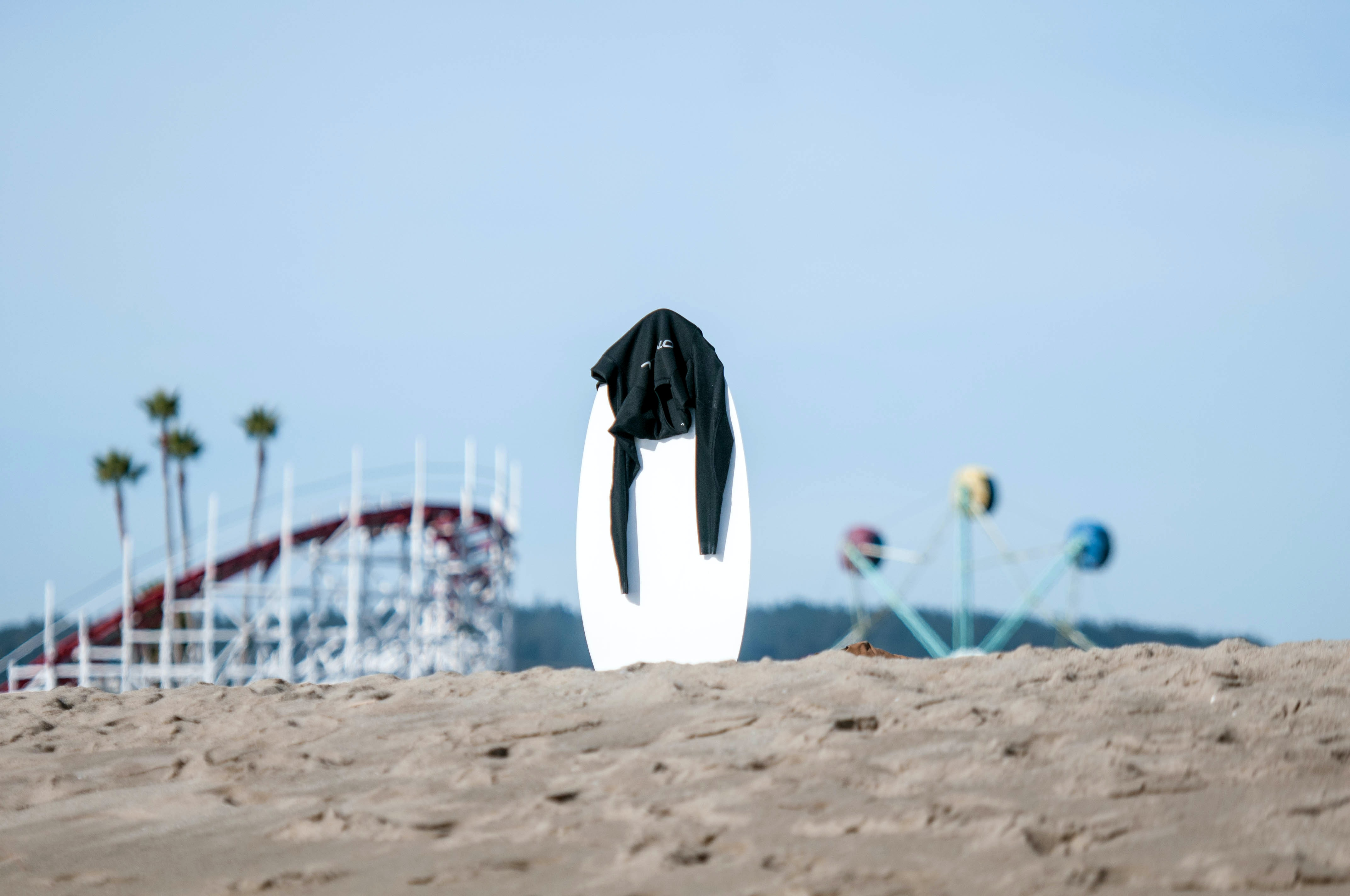 white surfboard with black rashguard on top in the middle of sand