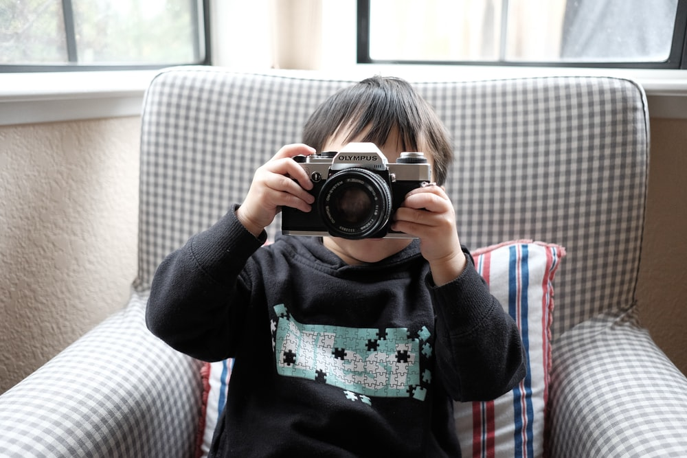 boy holding DSLR camera