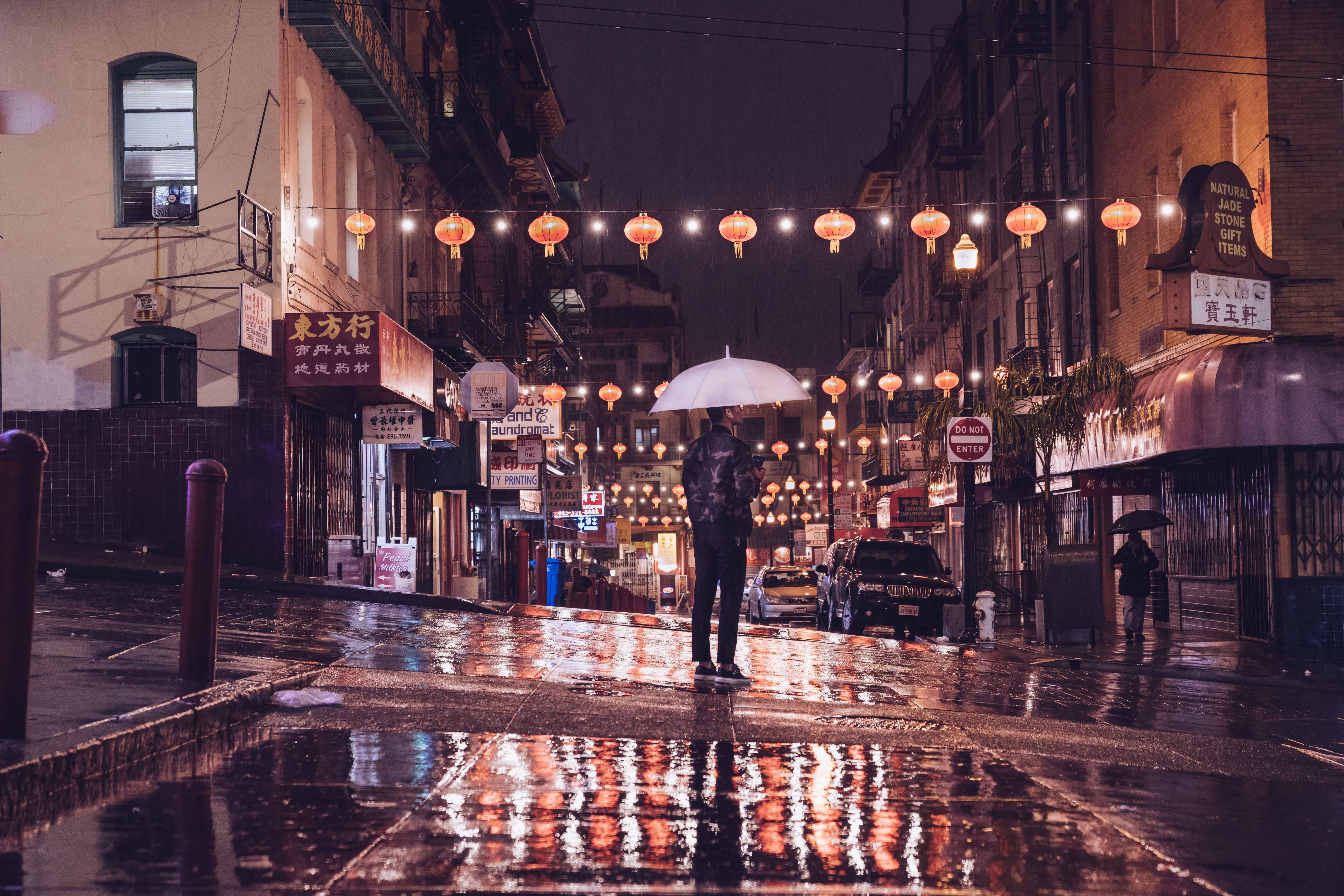 person standing on street holding umbrella during night time