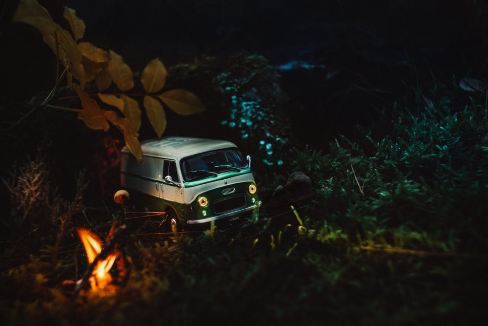 white vehicle passing road near trees at night time