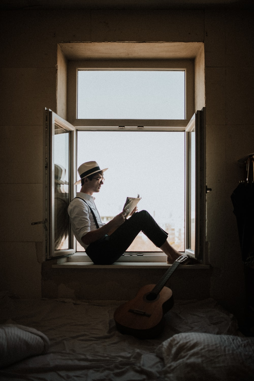 man sitting on window while reading