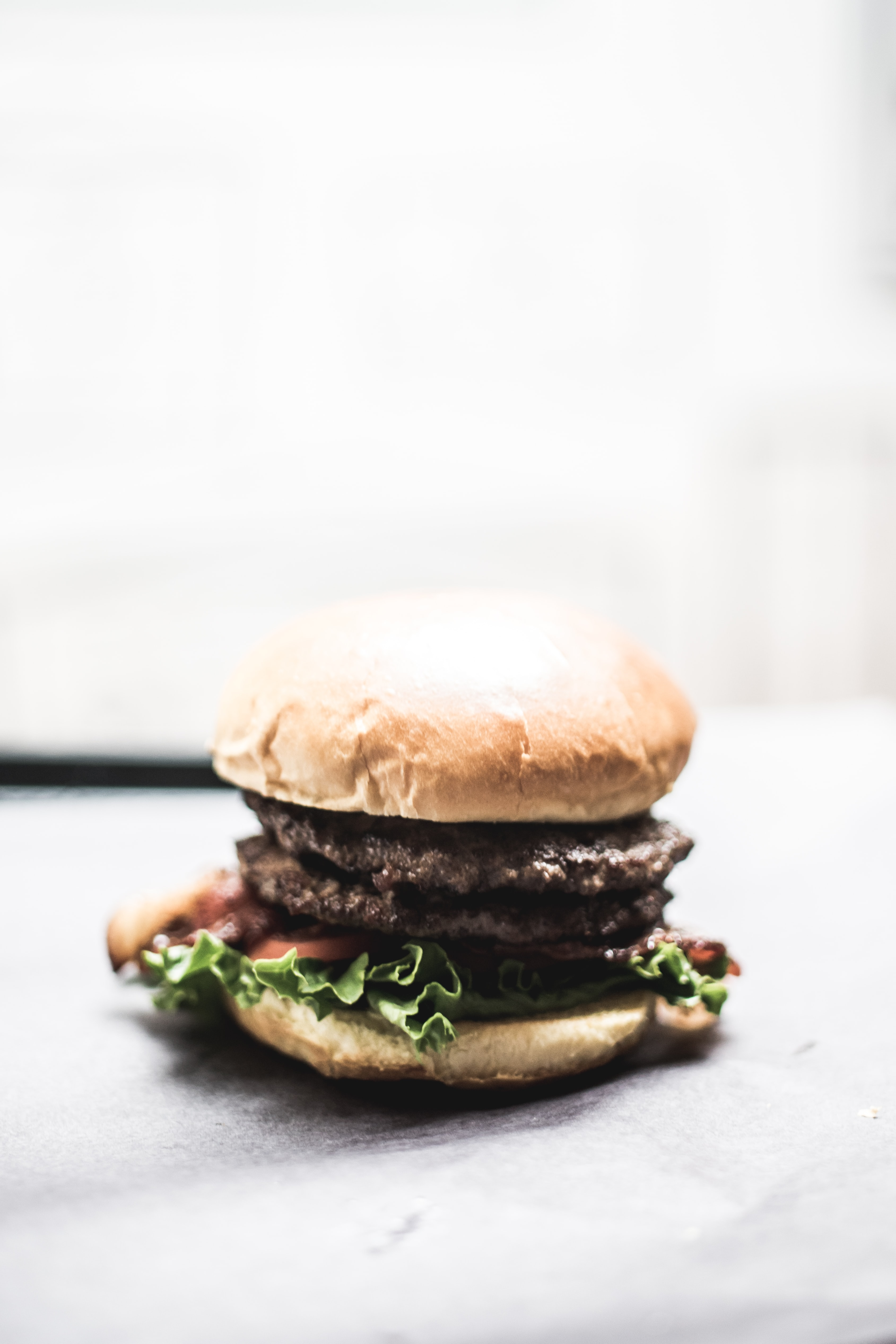 burger with lettuce and tomato on grey surface