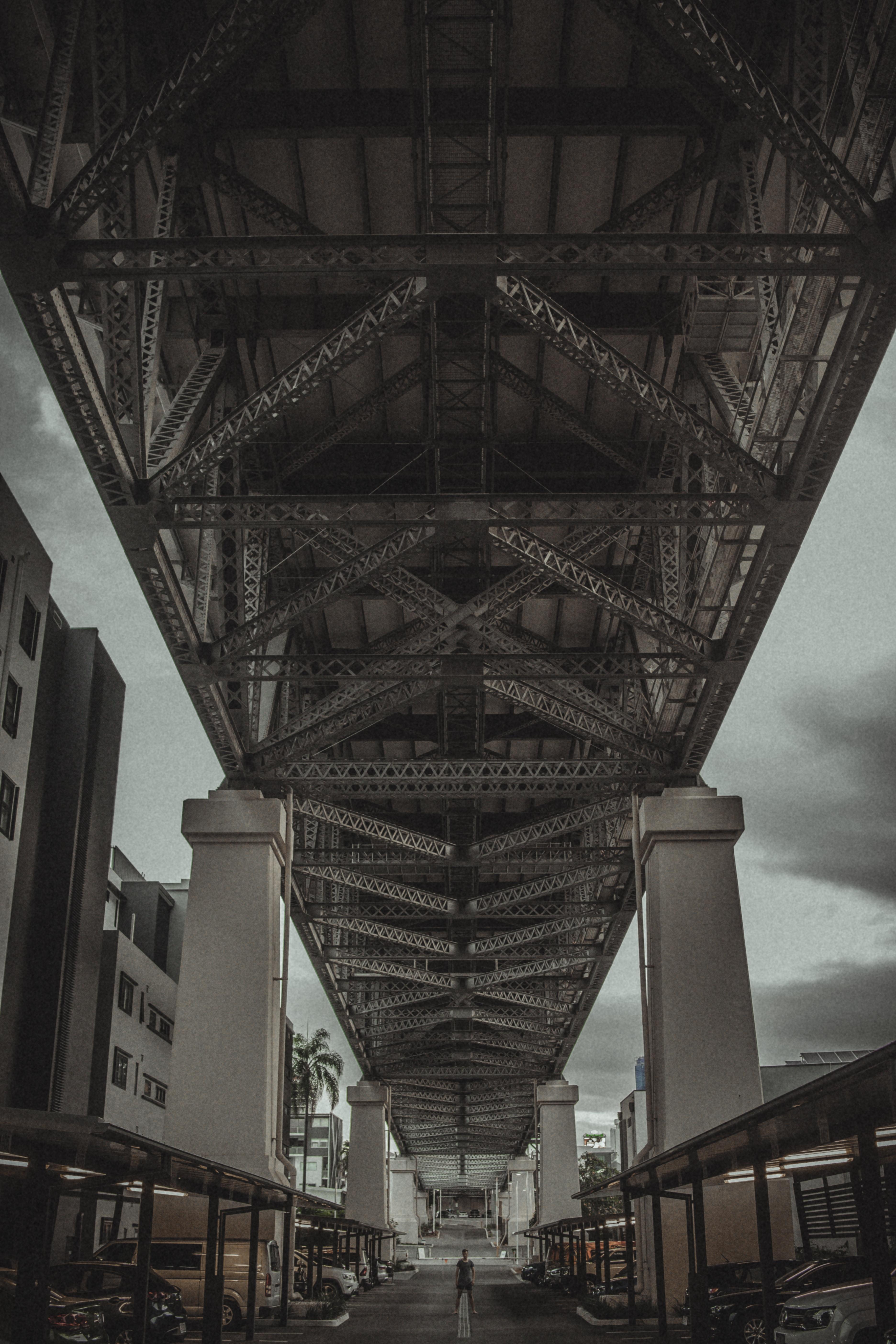brown metal bridge under cloudy sky