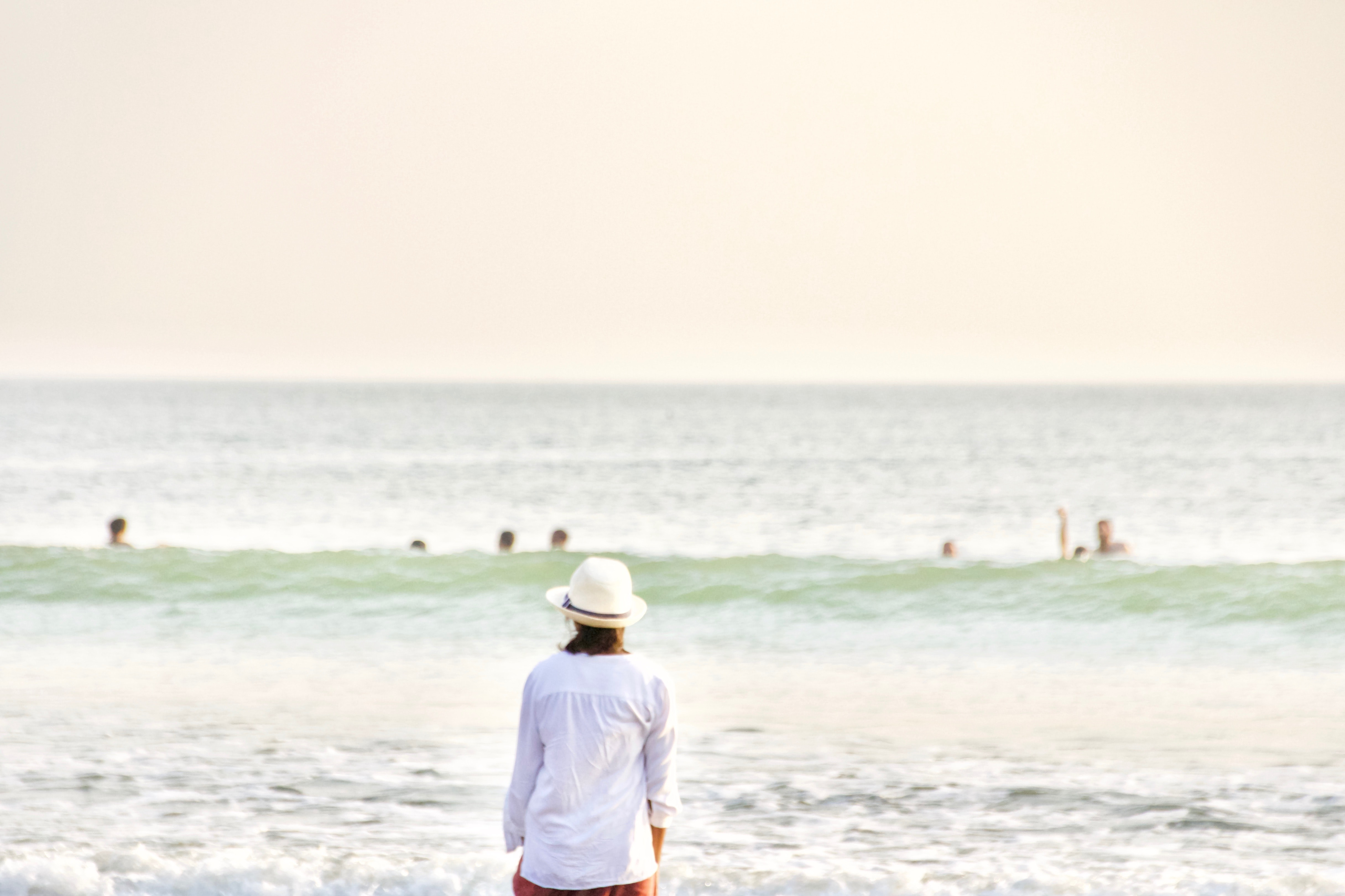 person with hat standing front of sea at daytime