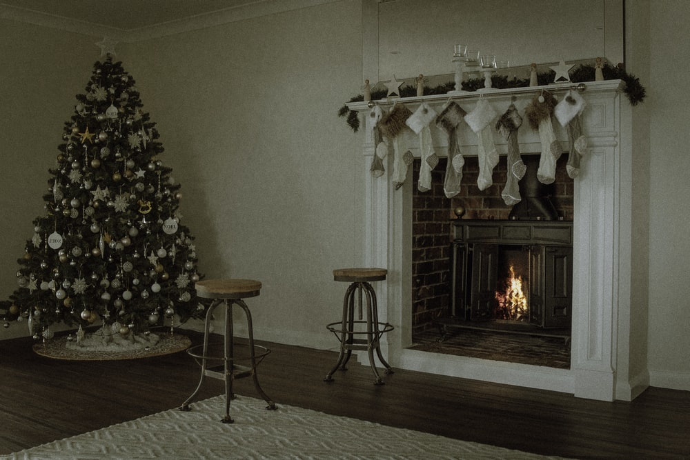 Christmas tree near two barstools at fireplace