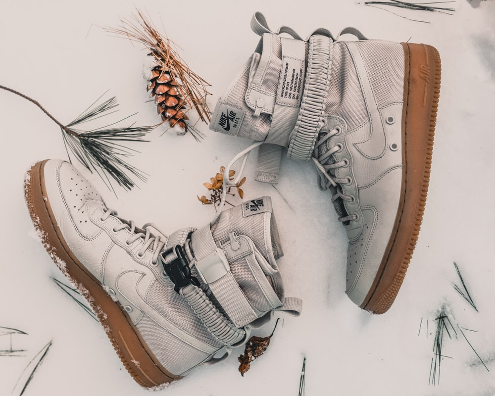 pair of gray Nike high-top sneakers on snow