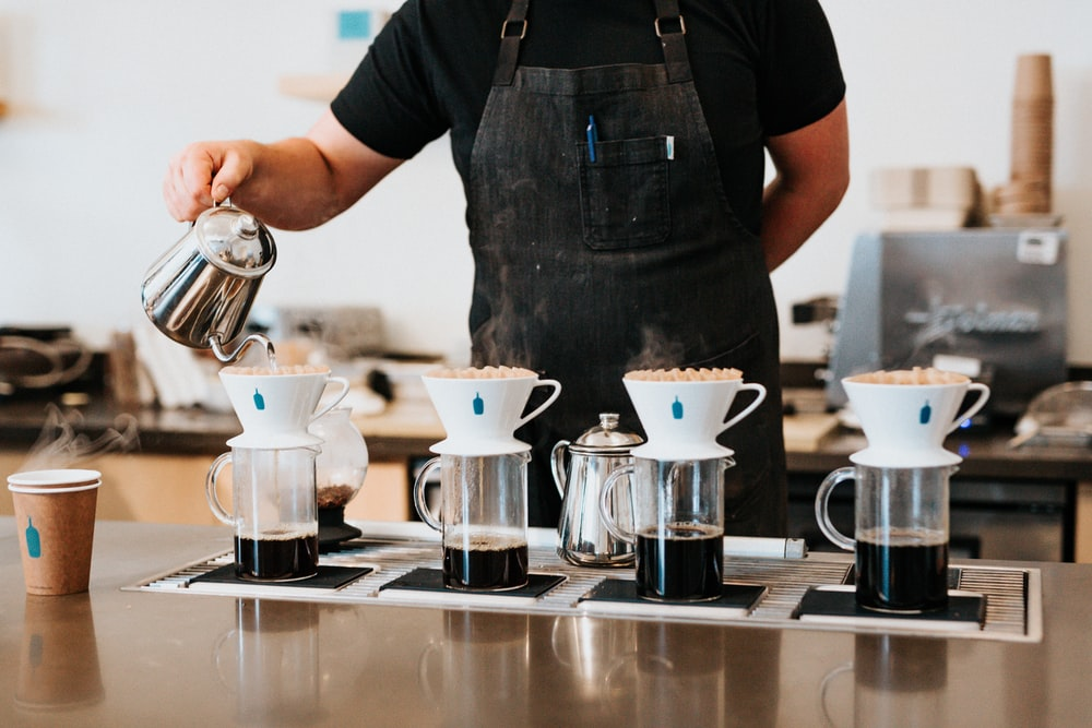 barista pouring hot water in cup