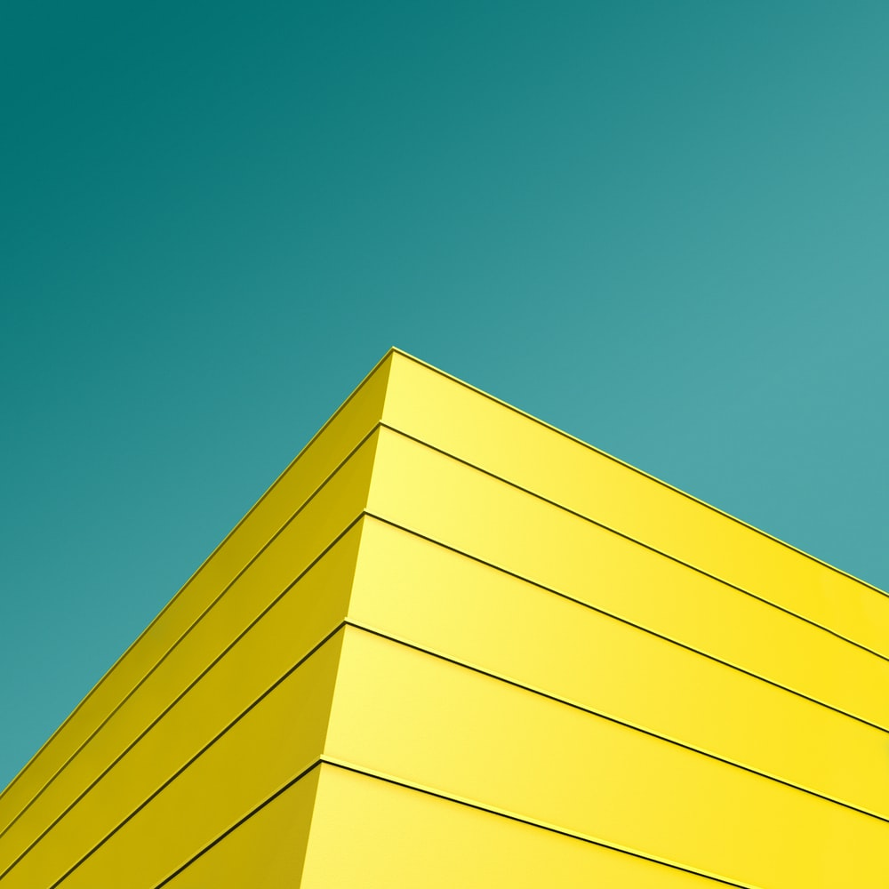 low angle photo of yellow and black striped building's corner