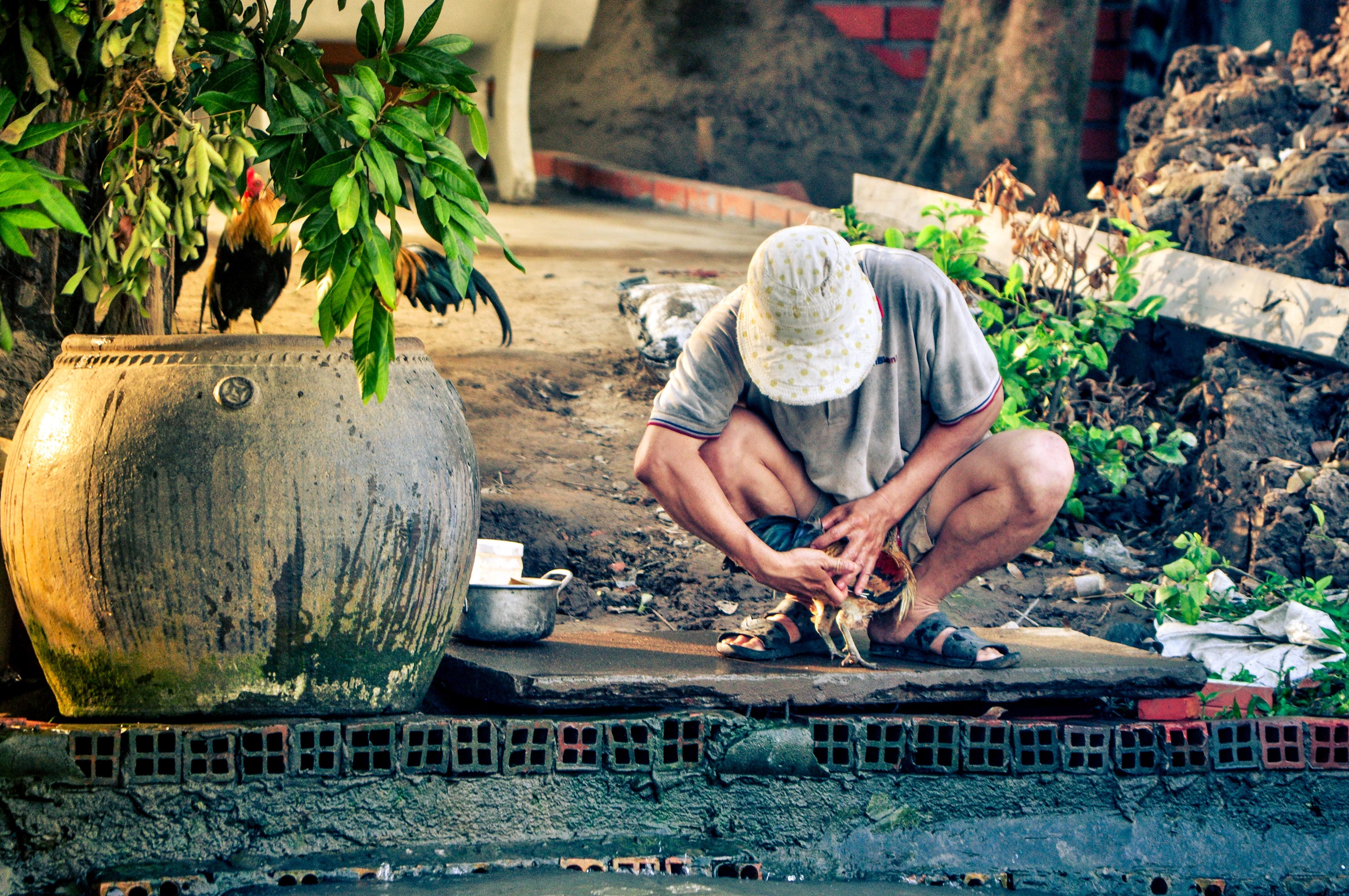 painting of man sitting on ground beside floor vase