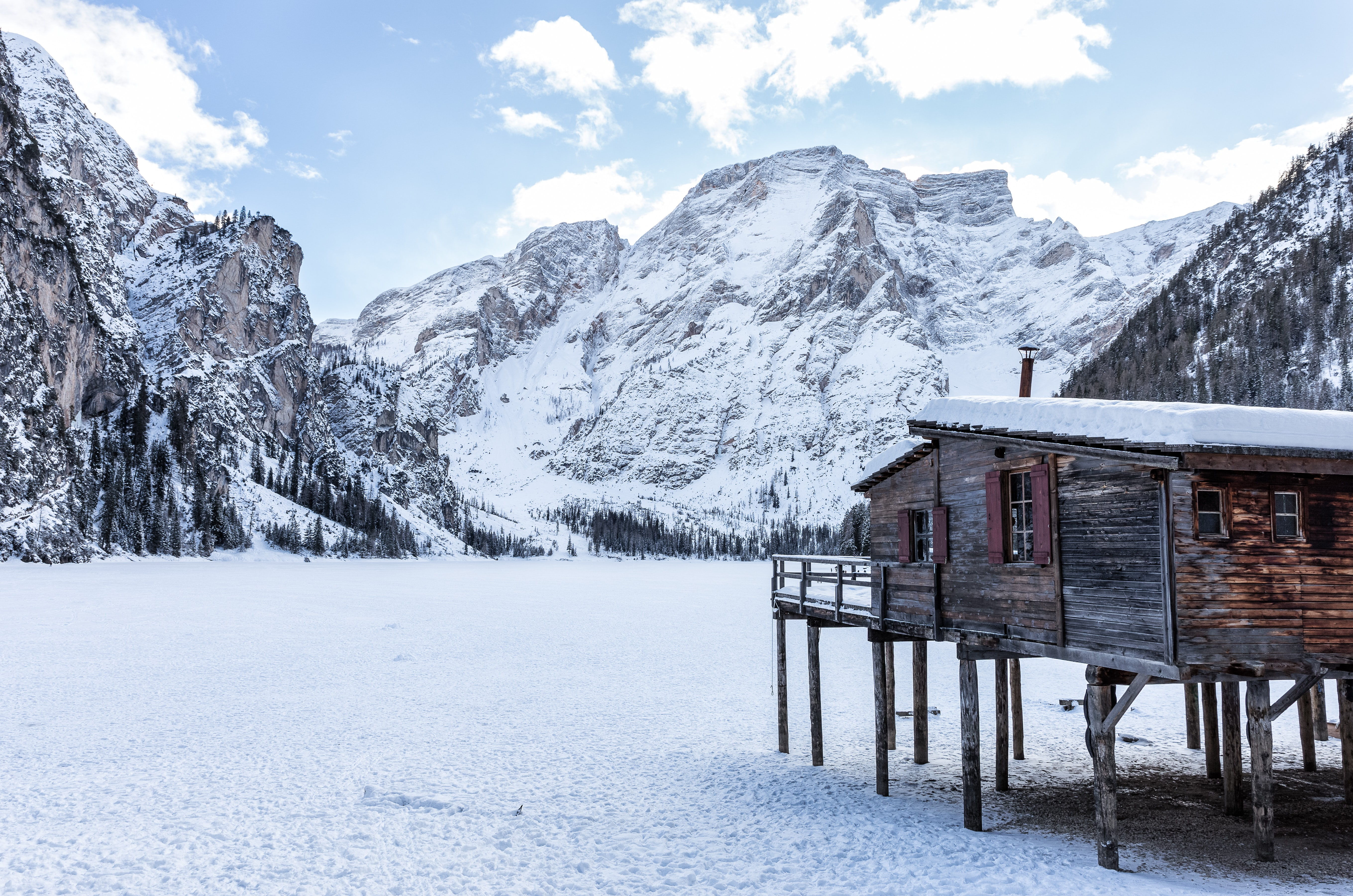 brown wooden house near mountains covered with snow at daytime