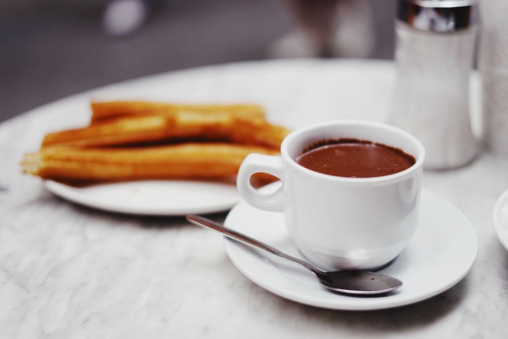 cup of chocolate drink with plate of churros