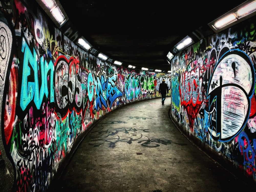 man walking on hallway with graffiti walls