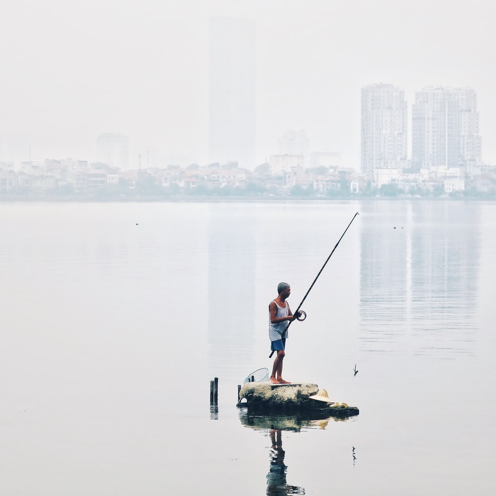 man standing in rock holding fishing rod