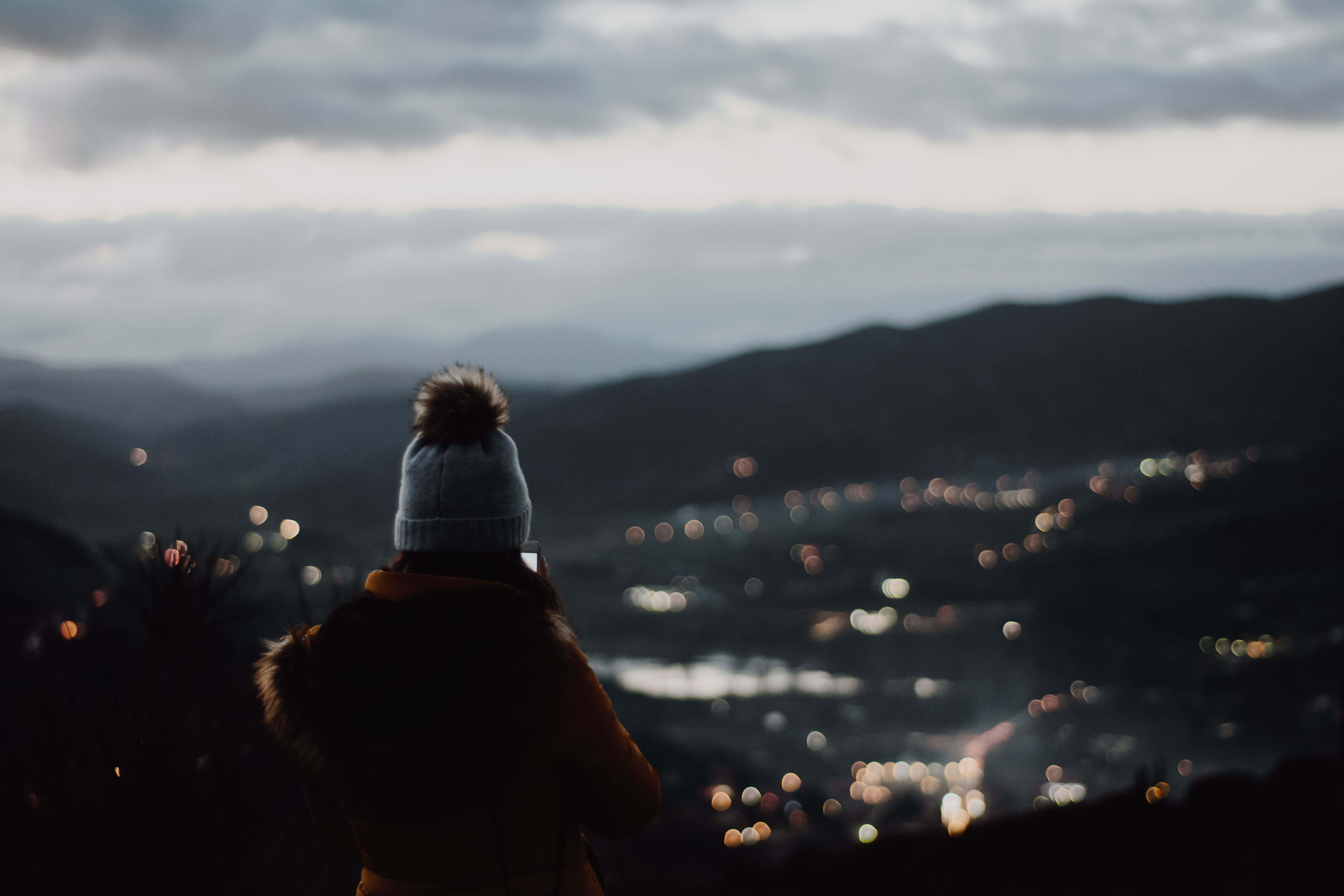 person standing on cliff with city lights as view