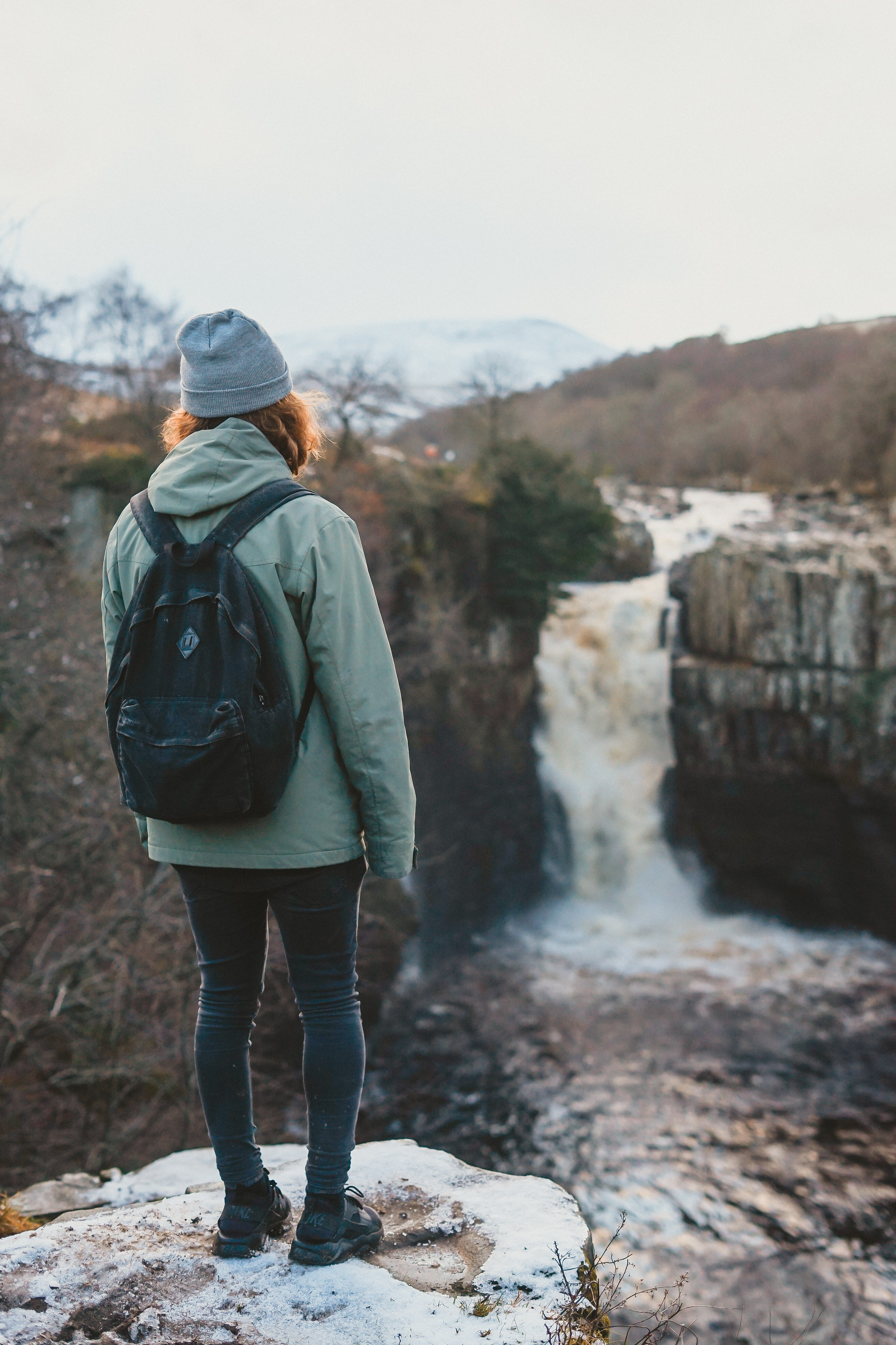 woman standing on cliff facing waterfall