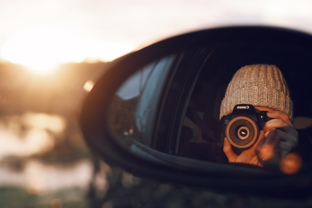 vehicle's side mirror reflecting person taking photo using Canon DSLR camera