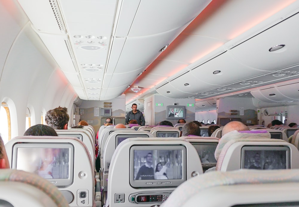 man walking down the aisle of airplane
