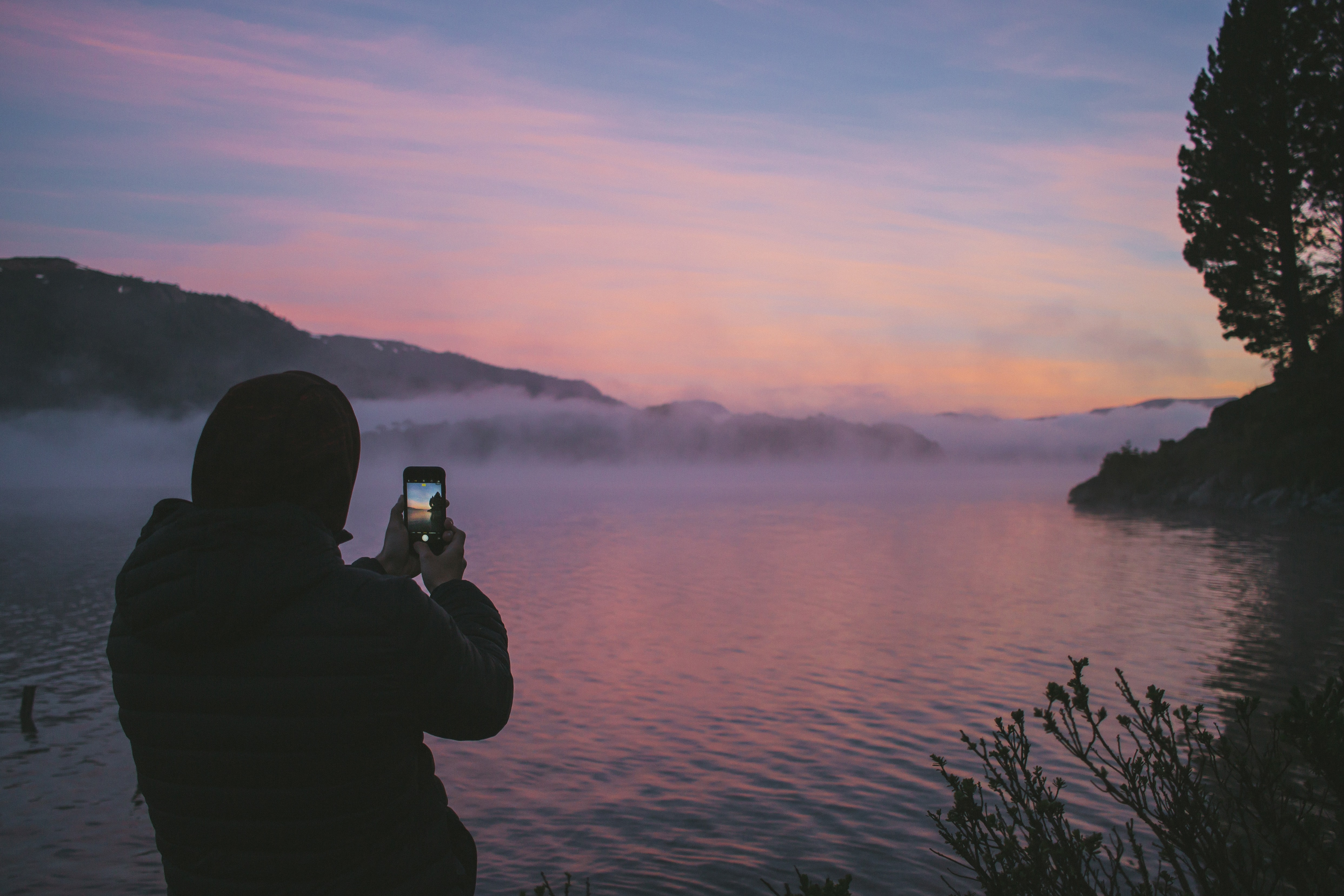 person taking photo of foggy river