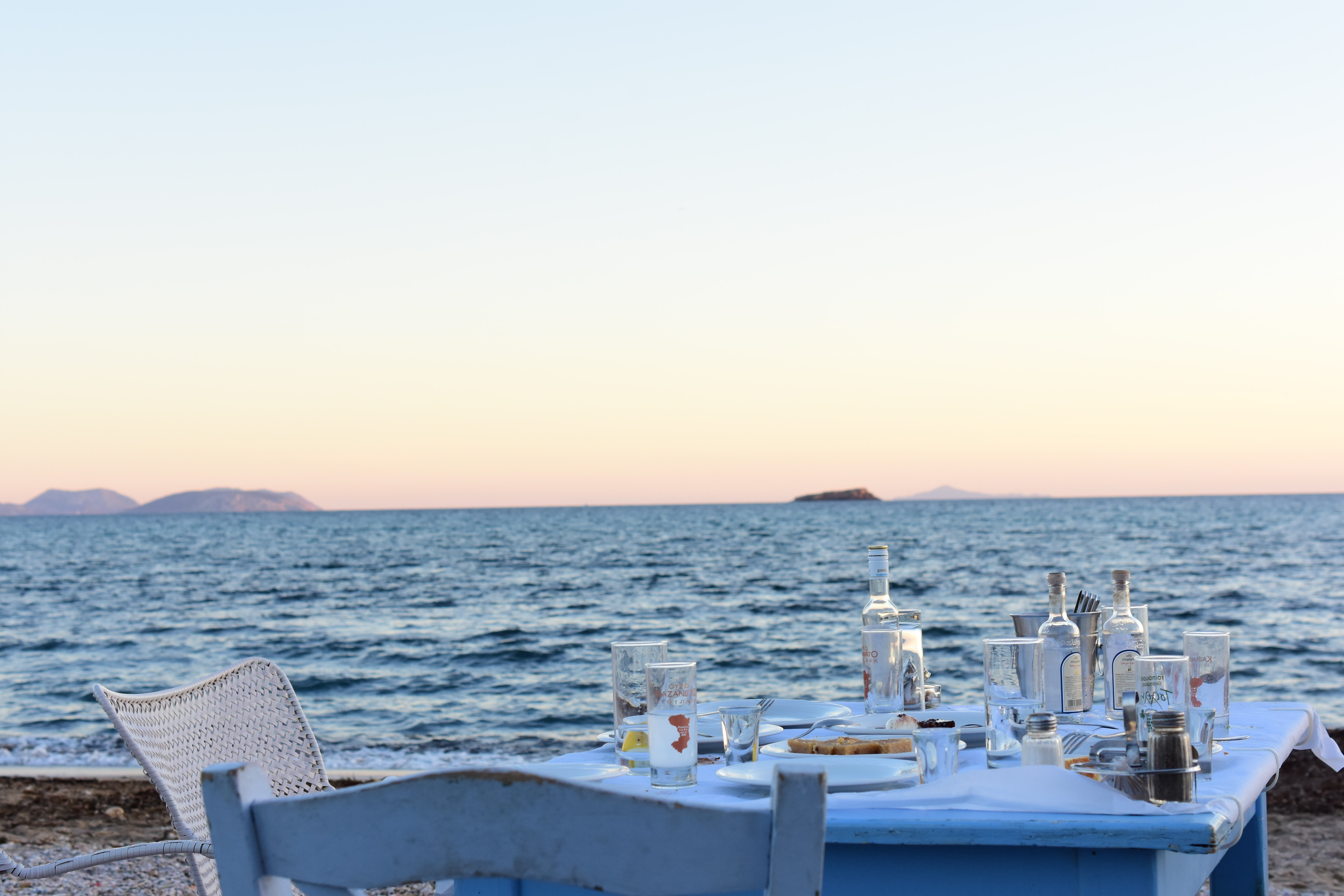 blue table with white chair near body of water