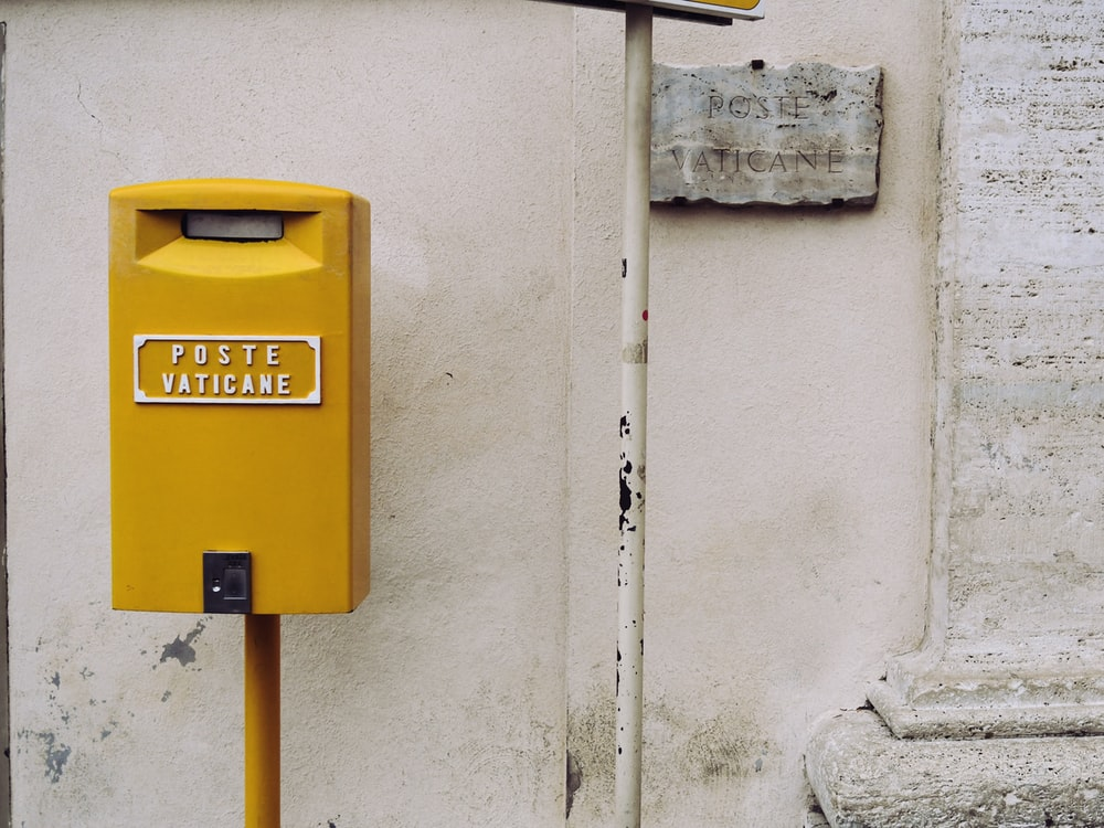yellow poste vaticane meter beside white wall