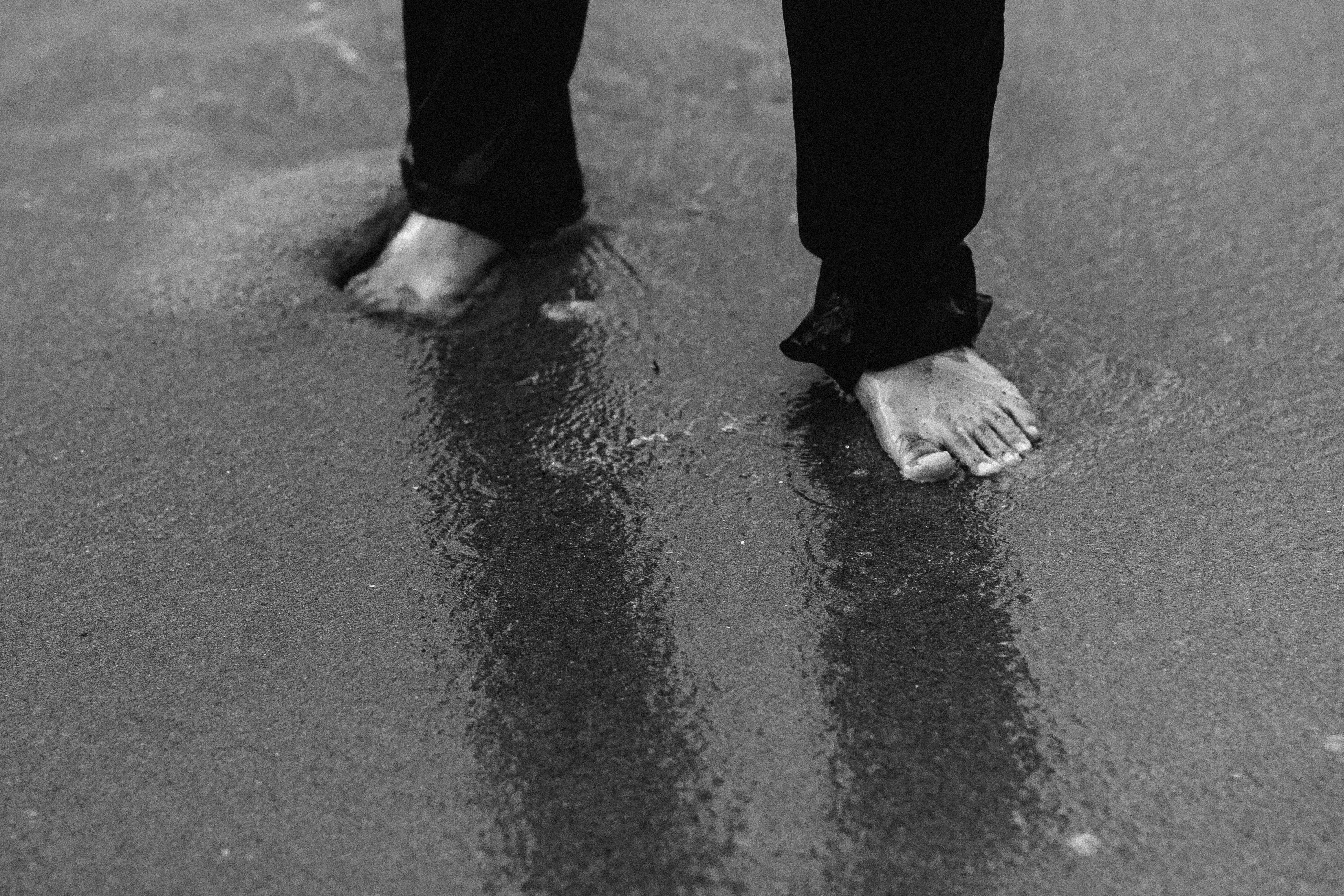 barefooted person wearing pants standing on wet sand