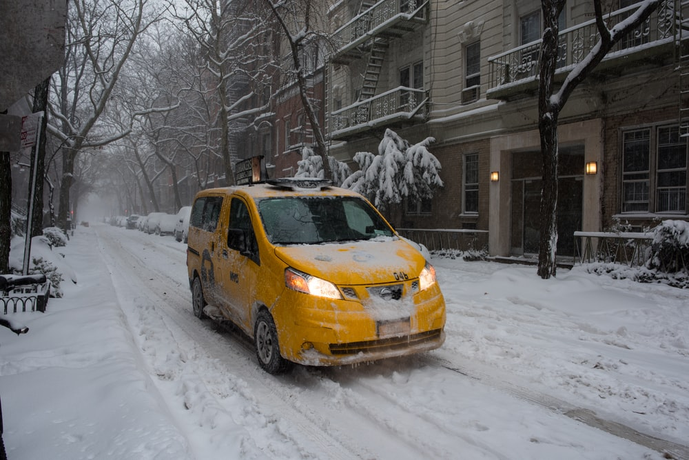yellow sedan on snow covered road during daytime