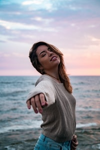 woman in grey sweater and blue denim bottoms reaching out arms and slightly looking up at beach under pink and blue sky