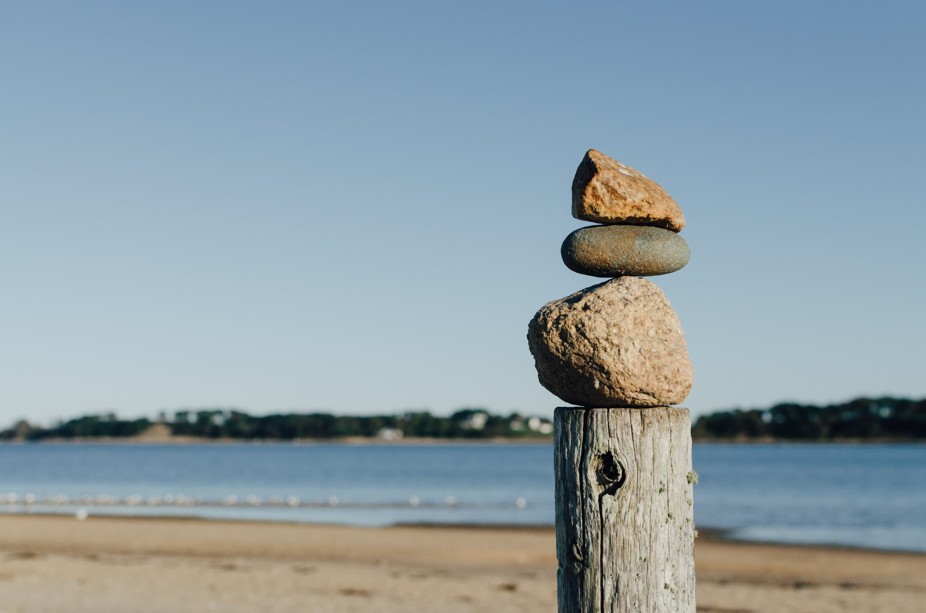 rock balancing on wooden post near body of water