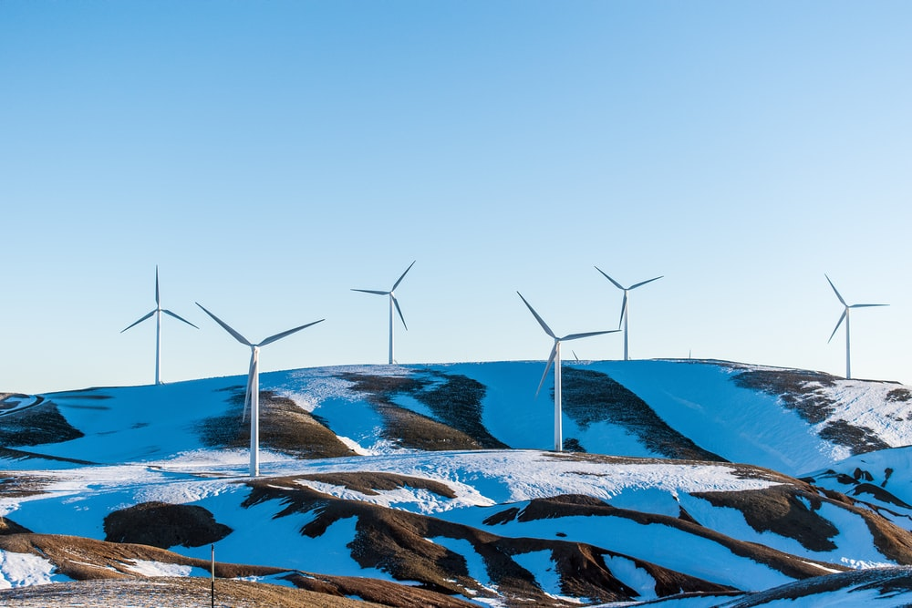 windmills surrounded by snow-covered field during daytime