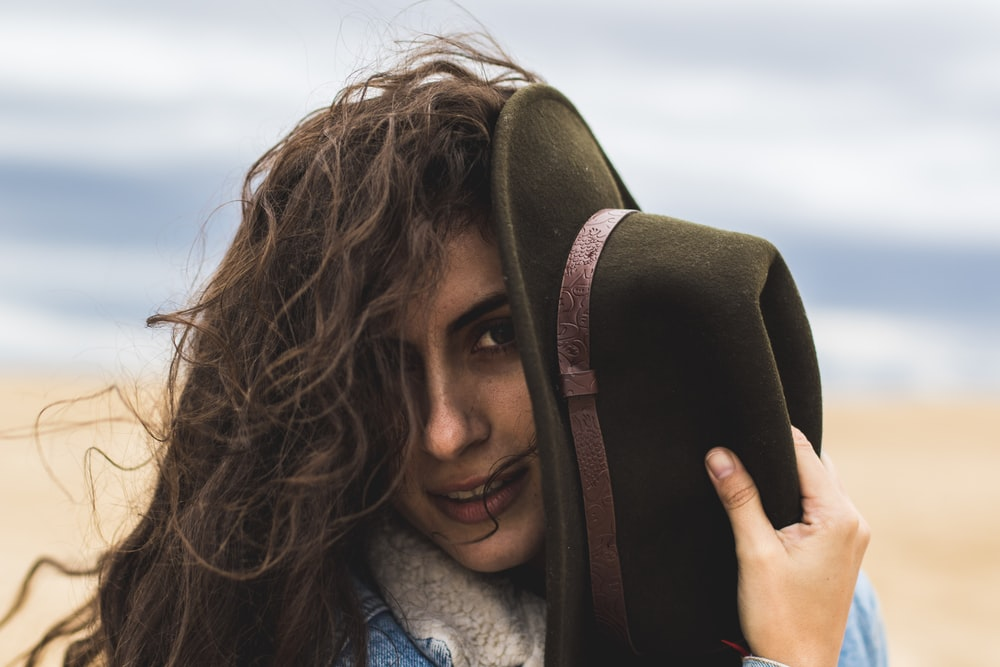 woman holding black hat on seashore during daytime