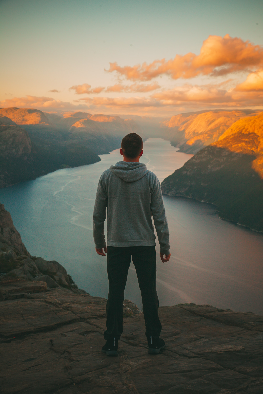 man wearing grey hoodie standing on mountain looking at river