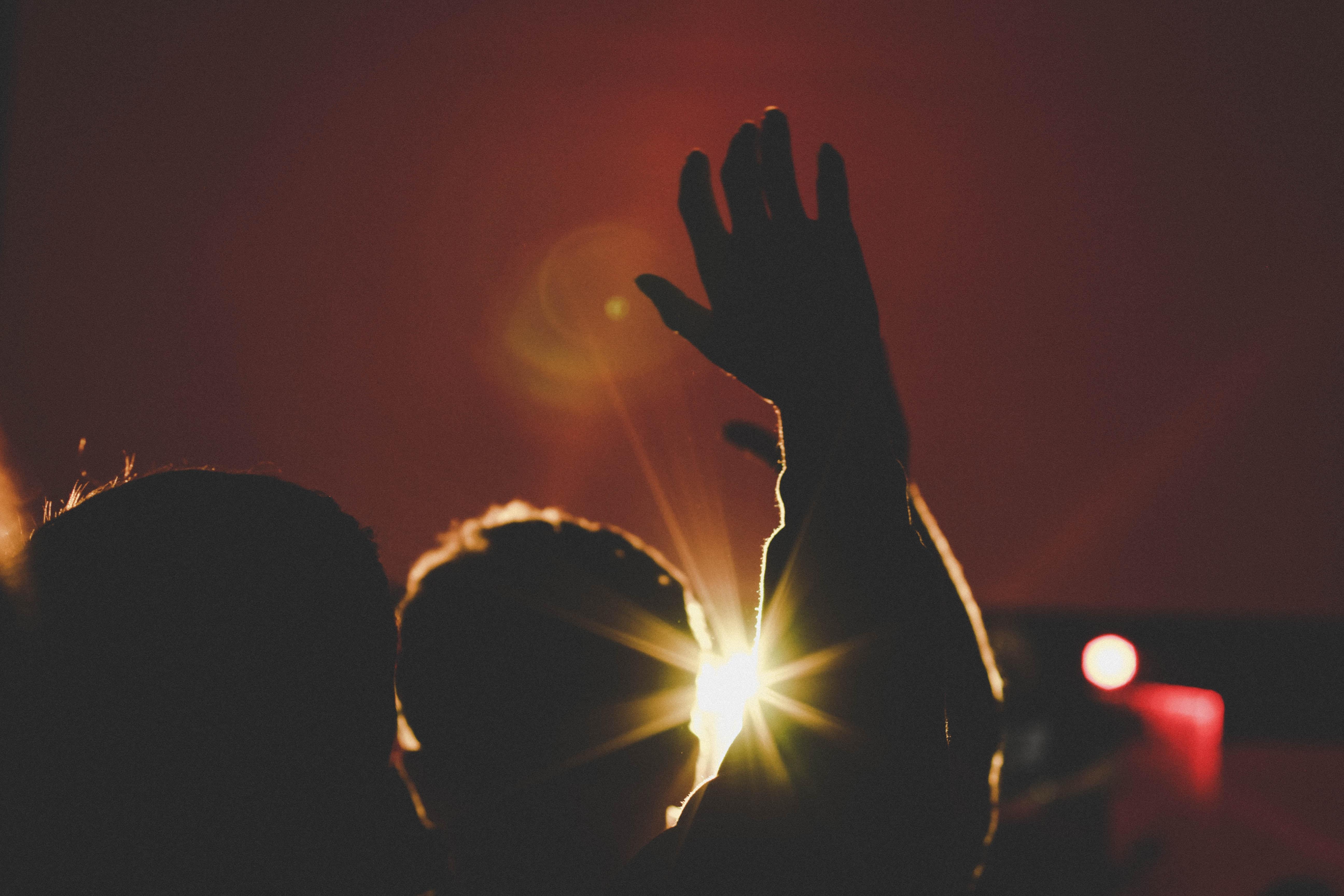 silhouette of man raising his hands inside deemed room