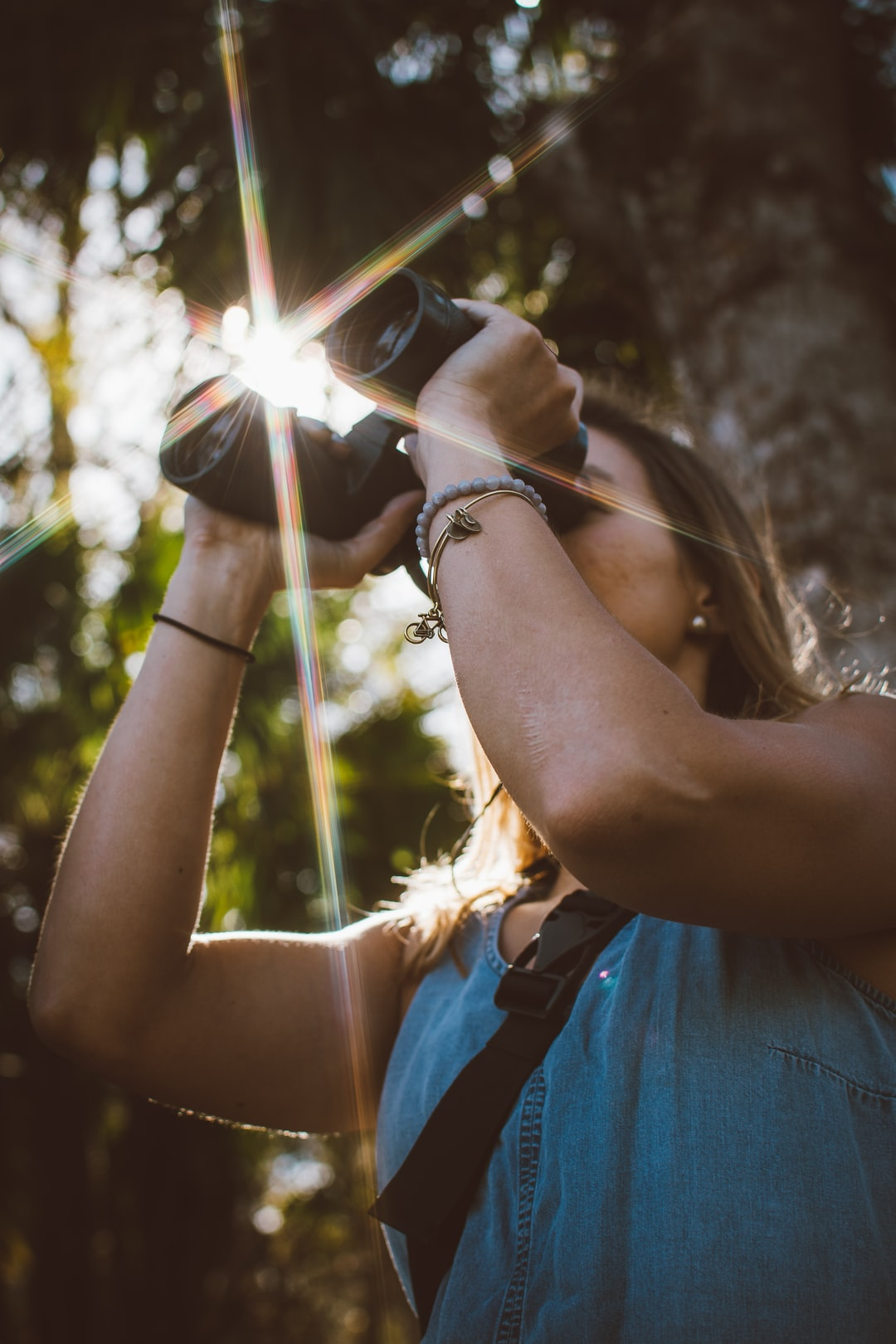 woman using binoculars in forest