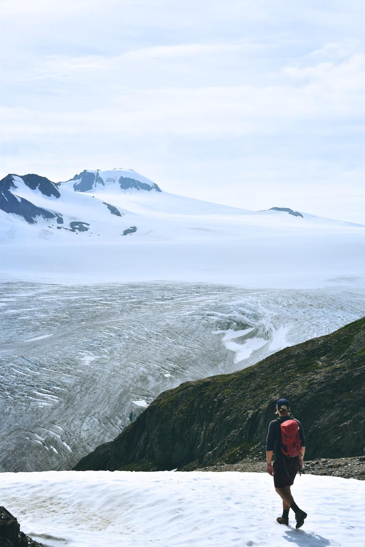 man walking on snow facing mountain