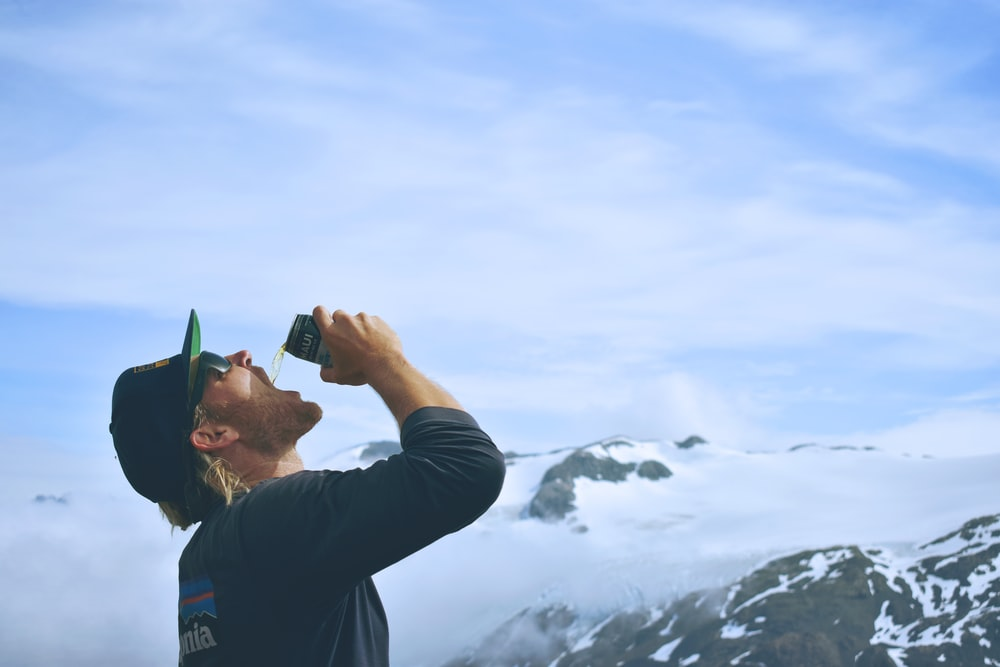 person drinking beverage in front of mountain covered by clouds